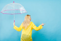 Woman wearing raincoat holding umbrella pointing Royalty Free Stock Photography