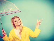 Woman wearing raincoat holding umbrella pointing Stock Photography