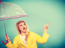 Woman wearing raincoat holding umbrella pointing Royalty Free Stock Images