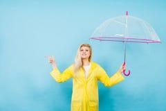 Woman wearing raincoat holding umbrella pointing Stock Photos