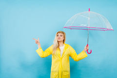 Woman wearing raincoat holding umbrella pointing Stock Photo