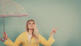 Woman wearing raincoat holding umbrella pointing Stock Image