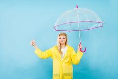 Woman wearing raincoat holding umbrella pointing Royalty Free Stock Photography