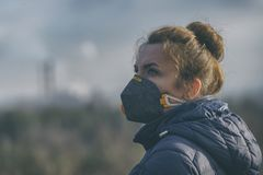 Woman wearing a real anti-pollution, anti-smog and viruses face mask royalty free stock photo