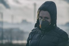 Woman wearing a real anti-pollution, anti-smog and viruses face mask stock image