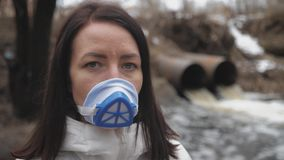 Woman wearing a real anti-pollution, chemical discharge into a river and viruses face mask. Dirty sewage from the pipe. Environmental pollution stock video footage