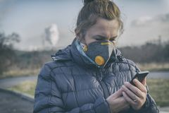 Woman wearing a real anti-smog face mask and checking current air pollution with smart phone app stock photo