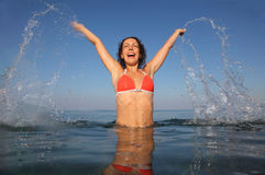 Woman wearing red bathing suit jumping in sea Stock Photo