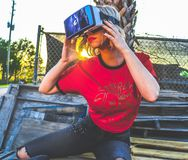 Woman Wearing Red and Black Top and Blue Distressed Bottoms Wearing Gray and Black Virtual Reality Sunglasses Royalty Free Stock Photography