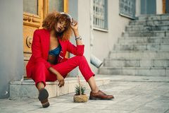 Woman Wearing Red Blazer and Pants Sitting on Marble Ground Stock Images