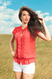 Woman wearing red blouse and white shorts while looking away Stock Photos