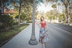 Woman Wearing Red and Blue Floral Tank Dress Beside Concrete Road stock photo