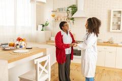 Woman wearing red cardigan feeling grateful to pleasant nurse. Pleasant nurse. Aged women wearing red cardigan feeling grateful to pleasant nurse taking care of stock image