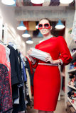 Woman wearing red dress in fashion store and silver purse Royalty Free Stock Image