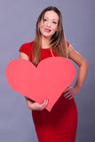 Woman wearing red dress holding big heart sign love symbol Royalty Free Stock Photo
