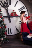 Woman wearing red dress near huge watch Royalty Free Stock Images