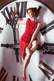 Woman wearing red dress near huge watch Stock Images