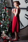 Woman wearing red dress near huge watch Royalty Free Stock Photography