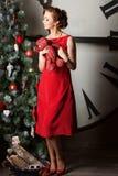 Woman wearing red dress near huge watch Stock Photography