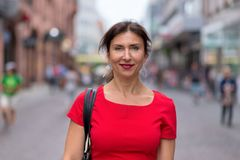 Woman wearing red dress and walking along road royalty free stock images