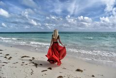 Woman Wearing Red Dress Walking on Seashore Under Blue and White Sky Royalty Free Stock Photos
