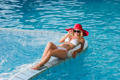 Woman wearing a red hat sitting in the pool Royalty Free Stock Photos
