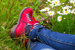 Woman wearing red hiking boots laying on a meadow Royalty Free Stock Photos