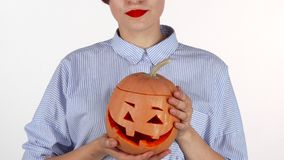 Woman wearing red lipstick holding up carved halloween pumpkin. Cropped studio shot of a woman smiling cheerfully, holding jack-o`-lantern isolated. Autumn stock video footage