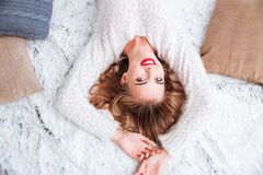 Woman wearing red lipstick and sweater lying on the carpet. Top view of a beautiful smiling woman wearing red lipstick and sweater lying on the carpet Stock Photography