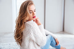 Woman wearing red lipstick and sweater sitting on the floor. Attractive young woman wearing red lipstick and sweater sitting on the floor Royalty Free Stock Photography