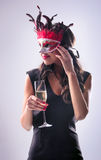 Woman wearing red mask at masquerade party drinking champagne Stock Image