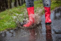 Woman wearing red rain boots jumping into a puddle. Close up Royalty Free Stock Photo