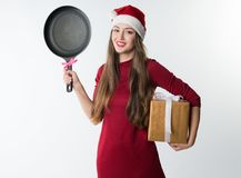 Woman wearing red santa claus hat with gift frying pan. Portrait of young christmas woman wearing red santa claus hat with gift frying pan isolated on white Royalty Free Stock Photos