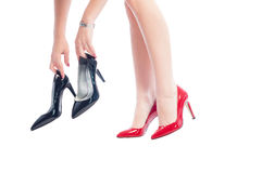Woman wearing red shoes holding black shoes Royalty Free Stock Image