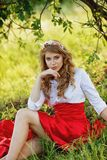 Woman wearing red skirt sitting under the tree Stock Photo