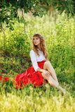 Woman wearing red skirt sitting under the tree Royalty Free Stock Images