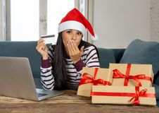Happy attractive woman buying christmas presents online using credit card looking excited stock photos