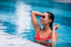 Woman wearing red swimsuit and sunglasses sitting in swimming pool, touching wet hair royalty free stock photos