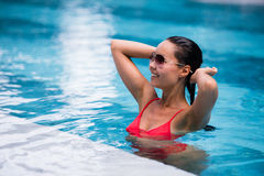 Woman wearing red swimsuit and sunglasses sitting in swimming pool, touching wet hair Royalty Free Stock Images