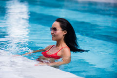 Woman wearing red swimsuit and sunglasses sitting in swimming pool, touching wet hair.  Stock Photography