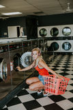 Woman Wearing Red Tank Top While Holding a Plastic Laundry Basket Royalty Free Stock Photography