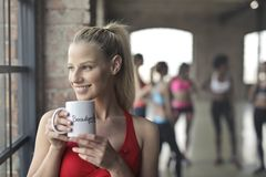 Woman Wearing Red Tank Top Holding White Ceramic Mug Stock Image