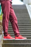 Woman wearing red trainers sportwear shoes. Unrecognizable woman wearing red trainers sportswear shoes and tracksuit during outdoor workout Royalty Free Stock Images