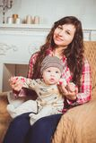 Woman Wearing Red And White Plaid Shirt Sitting On Chair Holding Baby royalty free stock photos