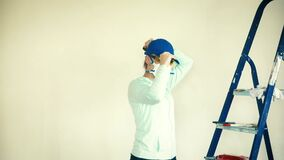 A woman wearing a respirator polishes a wall after applying plaster before painting