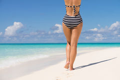 Woman wearing retro striped bikini and beach hat, enjoying amazi Royalty Free Stock Photo