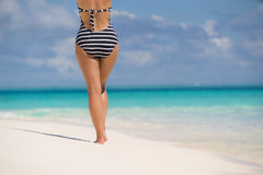 Woman wearing retro striped bikini and beach hat, enjoying amazi Royalty Free Stock Photos