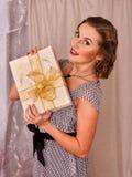Woman wearing retro style dress keeps gift box. Royalty Free Stock Image