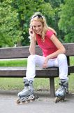 Woman wearing rollerblades calling. Young smiling woman wearing rollerblades calling with mobilephone outdoors Stock Photo