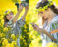 Woman wearing Romanian traditional blouse taking a selfie with a camera and checking her smart phone in canola field, outdoor shot Stock Photo